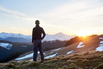 Rear view of male hiker watching wonderful scenery in mountains during spring colorful sunset