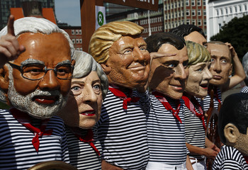 Activists from OXFAM wear masks depicting some of the world leaders during a demonstration at the harbor in Hamburg during the G20 summit