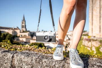 Woman holding a photo camera on the saint Emilion village background in France
