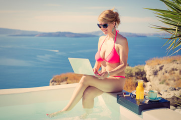 Woman working with laptop by the pool. Vintage photo filter.