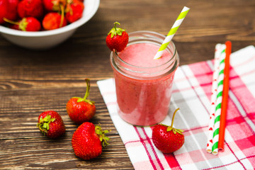 Healthy strawberry smoothie in mug with checkered cloth against rustic wood.