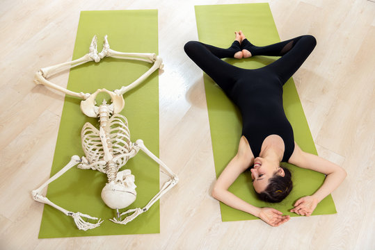 The girl is engaged in yoga along with the skeleton