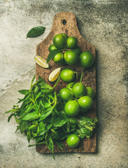 Flatlay of freshly picked organic limes and mint leaves for making cocktail or lemonade on wooden rustic board over grey concrete stone background, top view, vertical composition