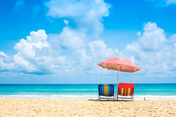 Beach chairs with umbrella and sand beach in summer.