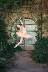 Ballerina dancing outdoors classic ballet poses in urban background