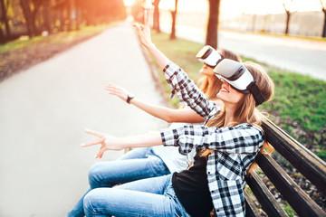 Two pretty girls enjoy virtual reality glasses outdoor
