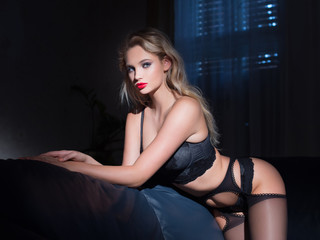 Sexy young blonde woman in underwear posing in dark