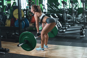Female fitness performing doing deadlift exercise with weight bar