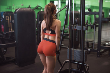sexy fitness woman execute exercise with exercise-machine Cable Crossover in gym