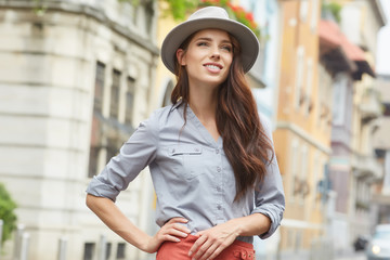 Close-up Fashion woman portrait of young pretty trendy girl posing at the city in Europe,summer street fashion,holding retro fedora hat popular until the 60s.laughing and smiling portrait.