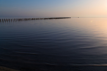 Golden lake surface at sunset  / Abandoned destroyed wooden pier in lake at sunset