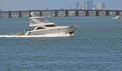 Upscale fishing boat cruising on the florida intra-coastal waterway with a Julia Tuttlle Causeway bridge and Miami high-rise buildings in the background