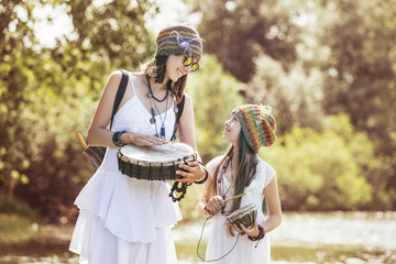 Beautiful and happy young mother and little daughter on nature with musical instruments bright Sunny day together