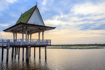 Wooden pavilion at lake with light on evening or sunset tone.