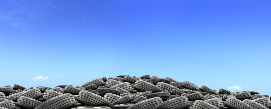 pile of used rubber tires with over light in blue sky background