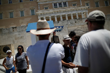 A Greek Presidential guard performs his sentry duty as tourists take pictures in front of the Unknown Soldier's Tomb with the parliament building seen in the background in Athens