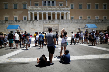 Tourists take pictures in front of the Unknown Soldier's Tomb with the parliament building seen in the background in Athens