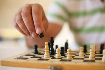 Senior man playing chess, close-up of hand.