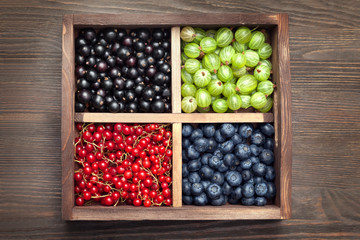 Red black currant blueberry gooseberry in a wooden box on an old table