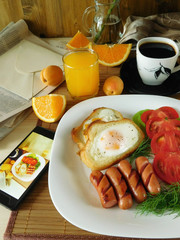 Fried eggs with sausages on a white plate and a smartphone with a photo of the meal in the screen. Breakfast concept