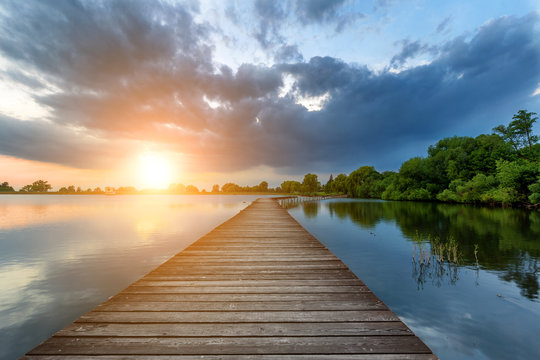 Wooden path bridge over lake at stormy dramatic sunset