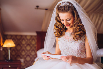 Young beautiful bride is reading a letter from a groom