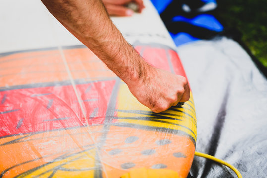 Close up view of hand waxing surf board outdoors.