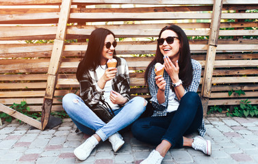 Two long hair brunette girls talking and eating ice cream outdoor