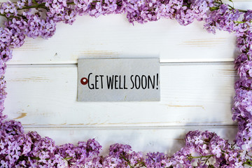 Beautiful purple lilac flower frame with get well soon sign on white wooden background