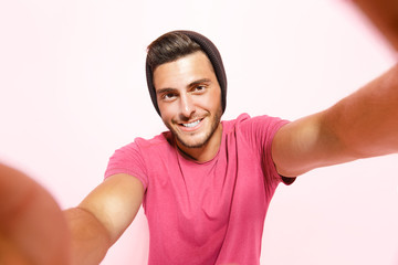 Handsome tanned guy with stubble wearing pink t-shirt and brown hat making selfie smiling.
