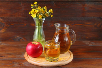 Apple juice and fruit on a dark wooden background.