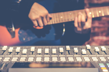 male musician playing acoustic guitar behind sound mixer in recording studio, focus on fader