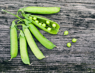 Pods of green peas on a old wooden surface close up, top view