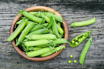 Pods of green peas in a round plate on an old wooden surface, top view