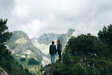 Couple looking over a valley with lake in the Switzerland Mountains