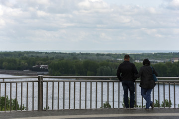 Couple standing on the observation deck over the river