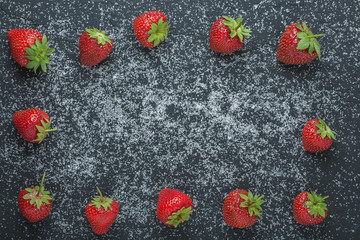 summer strawberry with sugar on black stone on top