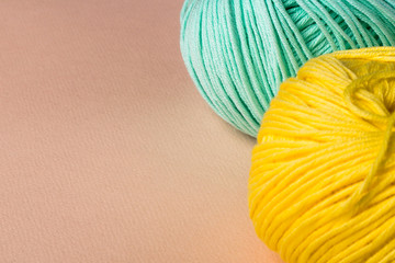 Turquoise and yellow tangle of thread on a pink background.