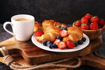 Delicious breakfast with fresh croissants and ripe berries on old marble background