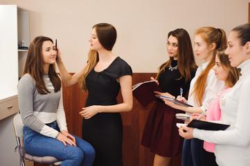 makeup teacher with her student girls. Makeup tutorial lesson at beauty school. Makeup master class