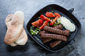 Cast-iron grill pan with balkan roasted cevapi sausages, fresh tomatoes, onion and pita bread, horizontal shot