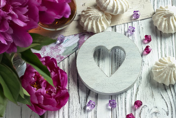 Peonies flowers pink glass of tea with white wooden heart marshmallow on a white wooden background - stock image.