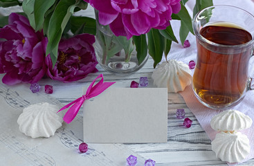 Peonies flowers pink glass of tea with greeting card marshmallow on a white wooden background - stock image.