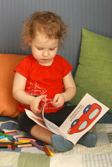Pretty little girl leafing a picture book