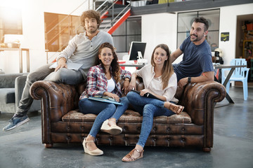 Group of trendy people sitting on couch in loft