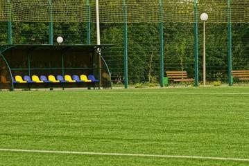 часть спортивного футбольного поля со скамейкой запасных