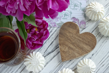 Peonies flowers pink glass of tea with brown wooden heart marshmallow on a white wooden background - stock image.