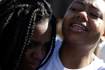 Girls react during the funeral of Santos in Rio de Janeiro