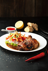 Delicious chicken confit with salad, lemon and ginger on a plate