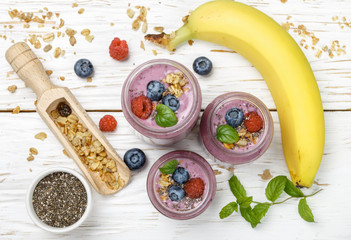 Healthy delicious smoothie from banana and fresh berries raspberry and blueberry granola with Chia seeds and mint leaves in portion jars